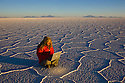 Bolivia, Altiplano, Salar de Uyuni, world's largest salt pan; woman sitting on hexagons working with laptop at sunrise --- Model Released