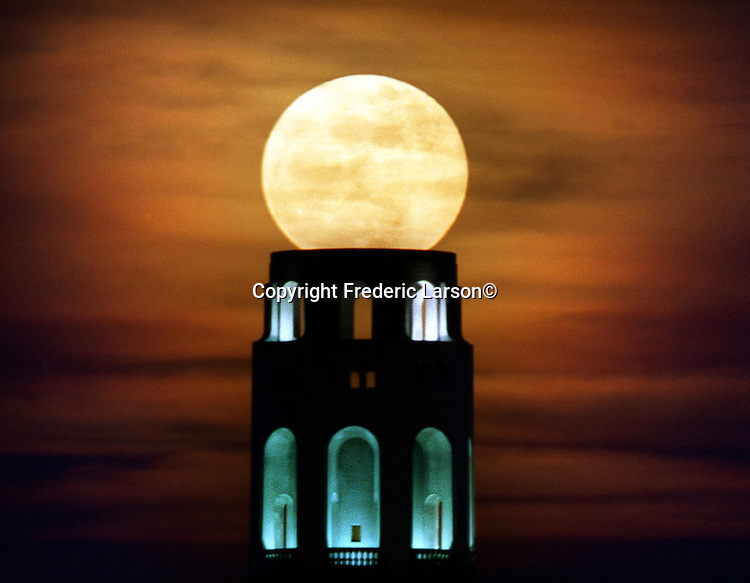 The full moon rose over the top of San Francisco's iconic Coit Tower with whisk of fog in the background.