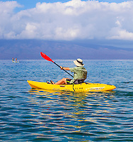 A kayaker paddles his kayak in the waters off of Ka'anapali Beach on Maui, with two standup paddlers in the distance.