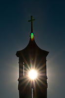 Afternoon sun shining through original church steeple in front of new St. Paul's Catholic Church.