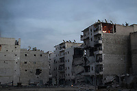 In this Wednesday, Dec. 05, 2012 photo, an appartment in fire is seen at the top of a destroyed building after it was shelled by mortar and tank artillery during heavy clashes between rebel fighters and the Syrian army in Aleppo, Syria. (AP Photo/Narciso Contreras)