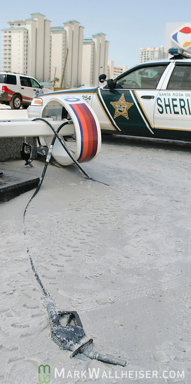 A Santa Rosa County Deputy Sheriff's car sits next to a damaged gas station on Navarre Beach July 11, 2005 as the empty gas hose lies buried in the sand  after Hurricane Ivan made landfall here yesterday.