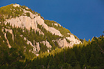 The sun shines on a rocky hill with a dark blue sky along the Smith River in Montana