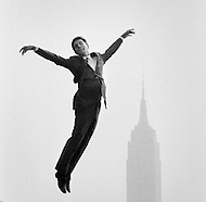 October 1966, Manhattan, New York City, New York State, USA. French singer Gilbert Becaud jumping with arms outstretched near the Empire State Building in New York. Image by © JP Laffont