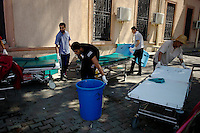 Tripoli, Libya, August 25, 2011.Volunteers clean beds outside the hospital main entrance. Tripoli central hospital operates under very difficult circumstances, lacking personnel and supplies such as medecines, oxygen and dressings.