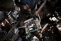 A man dismantles a circuit board to salvage components, at Agbogbloshie dump, which has become a dumping ground for computers and electronic waste from all over the developed world. Hundreds of tons of e-waste end up here every month. It is broken apart, and those components that can be sold on, are salvaged.
