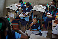 "Pupils at the Government Girls High School, Venugopalapuram, Cuddalore...Cuddalore's Government Girls High School is under-resourced with some student forced to sit on the floor for want of a desk. Though most classrooms are housed in a building that is only two years old, there is little ventilation to lessen the effects Cuddalore's tropical heat. The school does offer extra ""`bridge"" classes for those students recently arrived from village schools but staff are frequently absent from the school...Photo: Tom Pietrasik.Cuddalore town, Tamil Nadu. India.October 5th 2009"