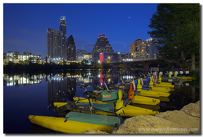 In the early hours of a tranquil Saturday morning in September, the Austin skyline comes to life from Ladybird Lake. These paddle boats are available for rent after the sun comes up. At this time, though, they were resting peacefully, waiting for the sun's arrival. In the distance, the iconic iconic Austin highrise, the Austonian, rises above the city. This Austin image was captured well before sunrise.