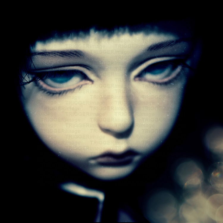 portrait of a sad doll with dark hair and blue eyes