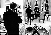 United States President Gerald R. Ford (behind the desk in the background) and United States Secretary of State Henry Kissinger (left foreground with back to camera), listen to a briefing by phone to them in the Oval Office at the White House in Washington, D.C. on May 14, 1975 from United States Secretary of Defense James Schlesinger from the Pentagon on the Cambodian incident involving the U.S. freighter Mayaguez.  Ford later sent United States Marines to rescue the ship and its 30 man crew.  The Marines sustained some casualties during the operation.<br /> Mandatory Credit: David Hume Kennerly / White House via CNP