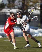 Boston College midfielder Caroline Margolis (21) on the attack as Boston University midfielder Louisa Del Rio (17) defends..Boston College (white) defeated Boston University (red), 12-9, on the Newton Campus Lacrosse Field at Boston College, on March 20, 2013.
