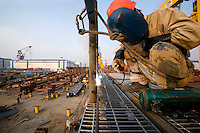 A worker welding a steel structure outside a factory, Changxing Island, Shanghai, China