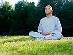 Shaolin monk meditating outdoors during sunrise sitting on green grass