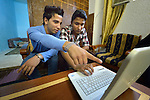 With help from his borther Ahmed (left), 18, Mahmoud Omar Abdul Aziz, 16, an Iraqi refugee, works on his computer at home using skills he learned in a center for Iraqi refugees in Zarqa, Jordan. He hopes to use his training in website design to earn income. The center is supported by International Orthodox Christian Charities, a member of the ACT Alliance...
