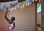 A woman hangs laundry on the porch of her family's new home in Camp Corail, a controversial resettlement of earthquake survivors north of Port-au-Prince, Haiti. Thousands of families were relocated to Corail from flood-prone areas of the capital in 2010, yet the promises of jobs that lured them there failed to materialize.