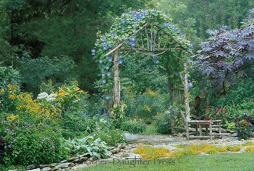 Handbuilt wooden arbor covered in blue flowers marking a transition from lawn to shade garden