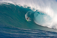 A tow-in surfer drops below the curl of Hawaii's big surf at Peahi (Jaws) off Maui.
