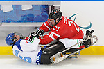 Raymond Grassi of Canada (21) checks a player on the Italian Sledge Hockey team during the game at UBC Thunderbird Arena.