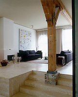 A set of steps leading to the open-plan living area is bisected by one of the original supporting beams of an apartment building in Amsterdam which was once a tramshed