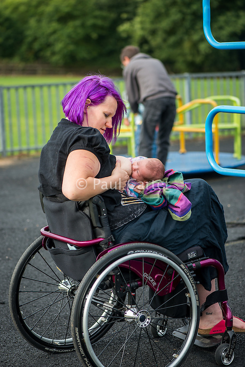A mother in a wheelchair breastfeeding her baby in a playground.