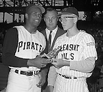Pittsburgh PA:  Roberto Clemente presenting a trophy to local baseball player from Pleasant Hills before the annual HYPO game at Forbes Field. The money raised by HYPO (Help Young Players Organize) was used to help local communities buy equipment and build ball fields.<br />