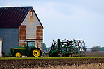 Summer storms approaching, a John Deere tractor and plow sit near an old barn on the prairie of rural Illinois.