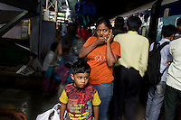 Razia Shabnam (in orange) arrives at her destination with her son Saihaan, to referee an all-India invitational boxing competition in the neighbouring town of Burnpur, Calcutta, West Bengal, India. Razia Shabnam, 28, was one of the first women boxers in Kolkata. She was also the first woman in her community to go to college. She is now a coach and one of only three international female boxing referees in India. Photo by Suzanne Lee for Panos London