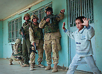 Soldiers from Killer Troop, 3rd Squadron, 3rd Armored Cavalry Regiment, allow women and children to exit the home of a suspected Fedayeen member near Hit, Iraq while raiding the building May 16, 2003. The troop conducted raids on two homes, capturing two suspected Fedayeen members who had allegedly put a bounty on the heads of American soldiers. They also confiscated some weapons and explosives. (Photo by Andy Rogers)
