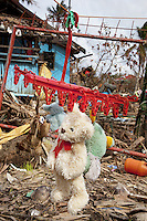 Philippines. Province Eastern Samar. Hernani. A teddy bear, a dog and two other stuffed animals are drying in the sun on a red plastic hanger among rubbles of a house dammaged by typhoon Haiyan's winds and storm surge. Typhoon Haiyan, known as Typhoon Yolanda in the Philippines, was an exceptionally powerful tropical cyclone that devastated the Philippines. Haiyan is also the strongest storm recorded at landfall in terms of wind speed. Typhoon Haiyan's casualties and destructions occured during a powerful storm surge, an offshore rise of water associated with a low pressure weather system. Storm surges are caused primarily by high winds pushing on the ocean's surface. The wind causes the water to pile up higher than the ordinary sea level. A stuffed toy is a toy sewn from a textile, and stuffed with a soft material. They are also known as plush toys, plushies, or stuffed animals and soft toys or cuddly toys. 26.11.13 © 2013 Didier Ruef