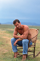handsome man sitting in a chair out in a field in New Mexico