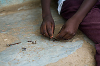 Clinton sorting a collection of rusted nails. He wants to be an engineer when he grows up. Clinton has  been recieving medical care for HIV  since 2003. He has yet to begin  ARVs.  His parents died within six months of each other from AIDS. They refused to be tested and never sought treatment.