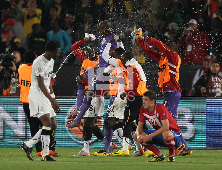 Ghana players soak their goalkeeper Richard Kingson as they celebrate winning against Serbia..