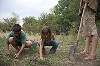 Saro Sarian's children dig potatoes in the garden of their home, which the family claimed in 1998 because it was abandoned.  They have been slowly renovating it since.