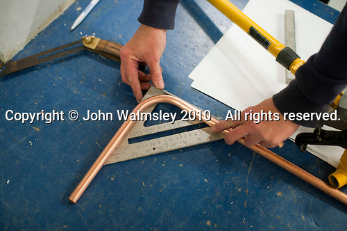 Plumbing student checking for accuracy, Able Skills, Dartford, Kent.