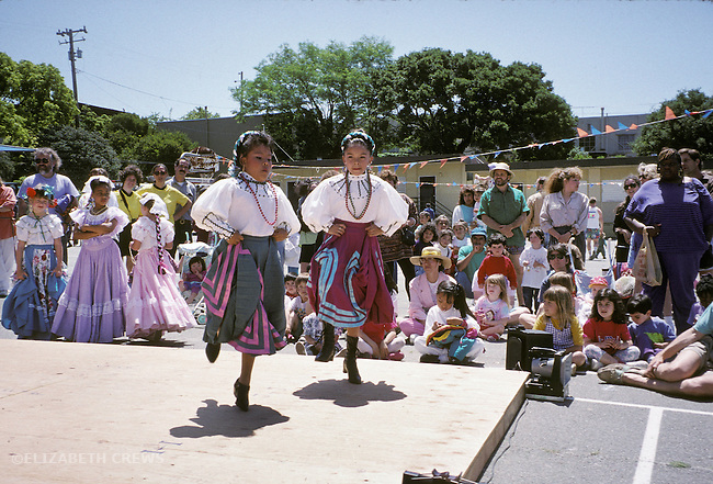 Berkeley CA Latina girls performing traditional dance in costume at school carnival