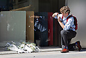 October 6, 2011: Tokyo, Japan - A foreign journalist takes a pictures of flowers left for the late Steve Jobs, founder and former CEO of Apple Inc., outside the Apple store in the Ginza shopping district of Tokyo. Jobs passed away in the United States at the age of 56 after a long battle with cancer. (Photo by Christopher Jue/AFLO)