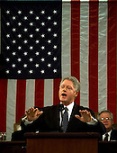 """United States President Bill Clinton delivers the State of the Union Address in front of the American Flag before a Joint Session of Congress in Washington, D.C. on January 19, 1999.  Clinton said, """"I stand before you to report that the state of our union is strong.""""  In the background at right is the Speaker of the U.S. House Dennis Hastert (Republican of Illinois).  .Credit: Win McNamee / Pool via CNP"""