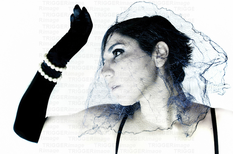 A young woman wearing black gloves and a veil
