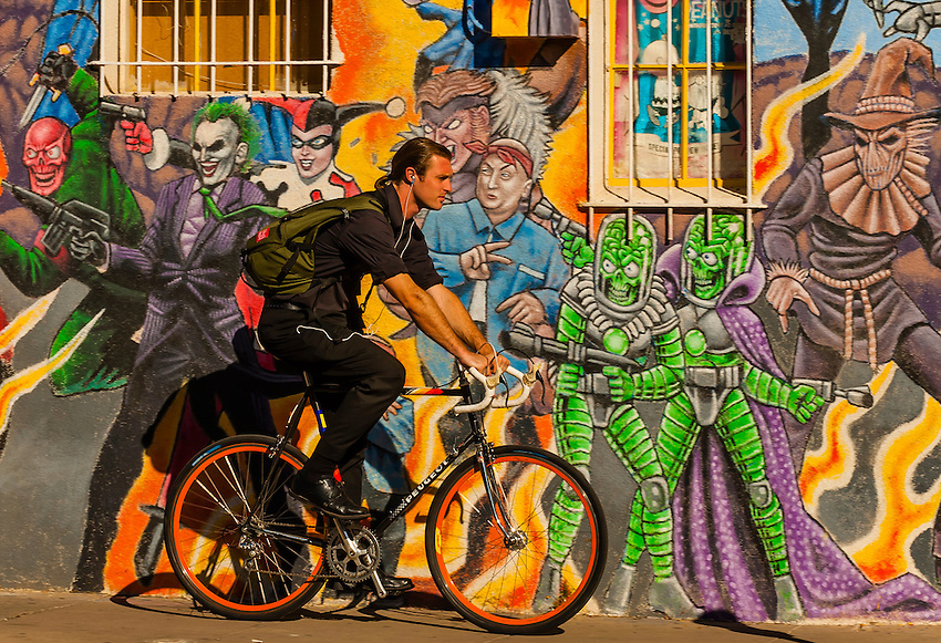 An urban bicyclist riding down the sidewalk with a mural for Comic book mural