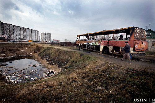 A man walks past a burnt bus that lays trashed in front of a wooden house on the road between Moscow and St Petersburg, near the town of Tver.