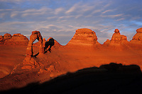 Delicate Arch casts its long shadow against the other hoodoo formations in the red bowl in which it sits, Arches National Park, Utah.