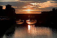 General view of the Ponte Vecchio, Florence, Tuscany, Italy, pictured on June , 2007, silhouetted against the sunset. The Ponte Vecchio, or Old Bridge, crosses the River Arno at its narrowest point. The original bridge, possibly Roman and first documented in 999, was swept away in a flood in 1117, rebuilt, swept away again in 1333 and rebuilt in 1345. In 1565 Cosimo de Medici commissioned Vasari to design a corridor, above the famous shops along the bridge, connecting the Palazzo Vecchio to the Pitti Palace. In 1593 the Medicis prohibited butchers, the traditional occupants, from the shops which were soon taken by Goldsmiths. Florence, capital of Tuscany, is world famous for its Renaissance art and architecture. Its historical centre was declared a UNESCO World Heritage Site in 1982. Picture by Manuel Cohen.