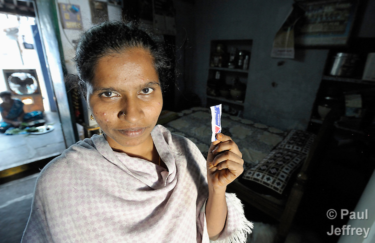Challa Rekha, 33, is HIV positive and holds a condom, which she uses when having sex with her HIV negative husband in Chilakaluripet, a town in Andhra Pradesh, India. Challa Rekha is an active participant in a local association of HIV positive people.