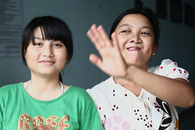 A girl waves while posing with a friend for a photograph at a center for children who have been affected by dioxin exposure in the village of Hoa Nhon, near Da Nang, Vietnam. The Da Nang Association of Victims of Agent Orange/Dioxin says that more than 1,400 children around the city suffer from mental and physical disabilities because of dioxin exposure, a legacy of the U.S. military's use of Agent Orange and other herbicides during the Vietnam War more than 40 years ago. About 60 children attend the Hoa Nhon center each day. Many of them have mental disabilities or they cannot hear or speak. Children are taught to read and write, sew clothes, make handicrafts and help their families raise crops and livestock. The Vietnam Red Cross estimates that 3 million Vietnamese suffer from illnesses related to dioxin exposure, including at least 150,000 people born with severe birth defects since the end of the war. The U.S. government is paying to clean up dioxin-contaminated soil at the Da Nang airport, which served as a major U.S. base during the conflict. But the U.S. government still denies that dioxin is to blame for widespread health problems in Vietnam and has never provided any money specifically to help the country's Agent Orange victims. May 29, 2012.