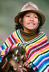 Quechua boy holding a puppy, Peru