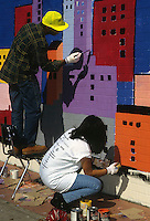 Volunteers from New York Cares paint a mural in a New York public school. (© Frances M. Roberts)