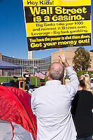 """A protester holds a sign reading """"Hey kids!  Wall Street is a casino …"""" while listening to Mark LeVine (of UCI) speak at the Occupy Orange County, Irvine camp on Saturday November 5."""