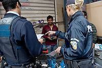 A police man and woman prepare to arrest two men hanging out on a street. According to UNHCR, 38,992 immigrants arrived in Greece in the first 10 months of 2010, whereas in 2009 the number was only 7,574.