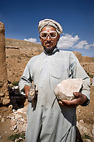 A stonecutter wearing protective goggles and holding a piece of rock and a hammer. He is working for the NGO People in Need (PIN).