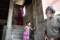 Palesinian man and his grand daughter and daughter showing their conditions of live and poor housing in the Shatila camp. Beirut, Lebanon. August 2015